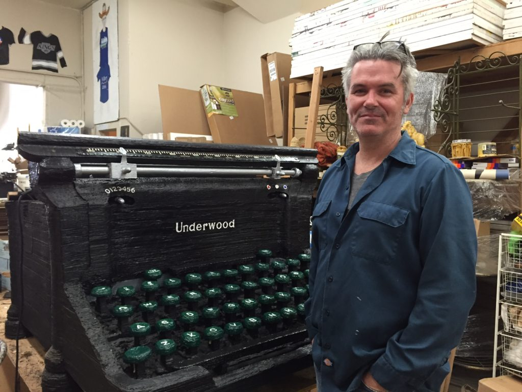 Hancock Park resident and artist Tim Youd stands in his studio with an oversized typewriter sculpture that is part of his 100 Novels Project. Youd will be re-typing John Rechy's Numbers from 11 a.m. to 4 p.m. at the Fern Dell entrance of Griffith Park July 6th through July 15th. Photo credit: Sheila Lane