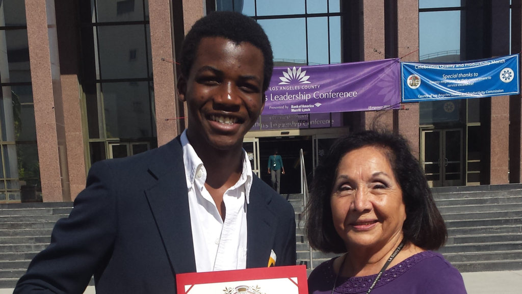 Oston Jemba Madengue (left) holds his Recognition Certificate with Olivia Rodriguez, the Executive Director of the Los Angeles County Domestic Violence Council.